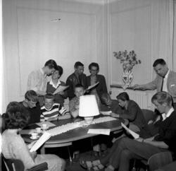 En samling männiksor sitter runt ett bord och sjunger tillsa