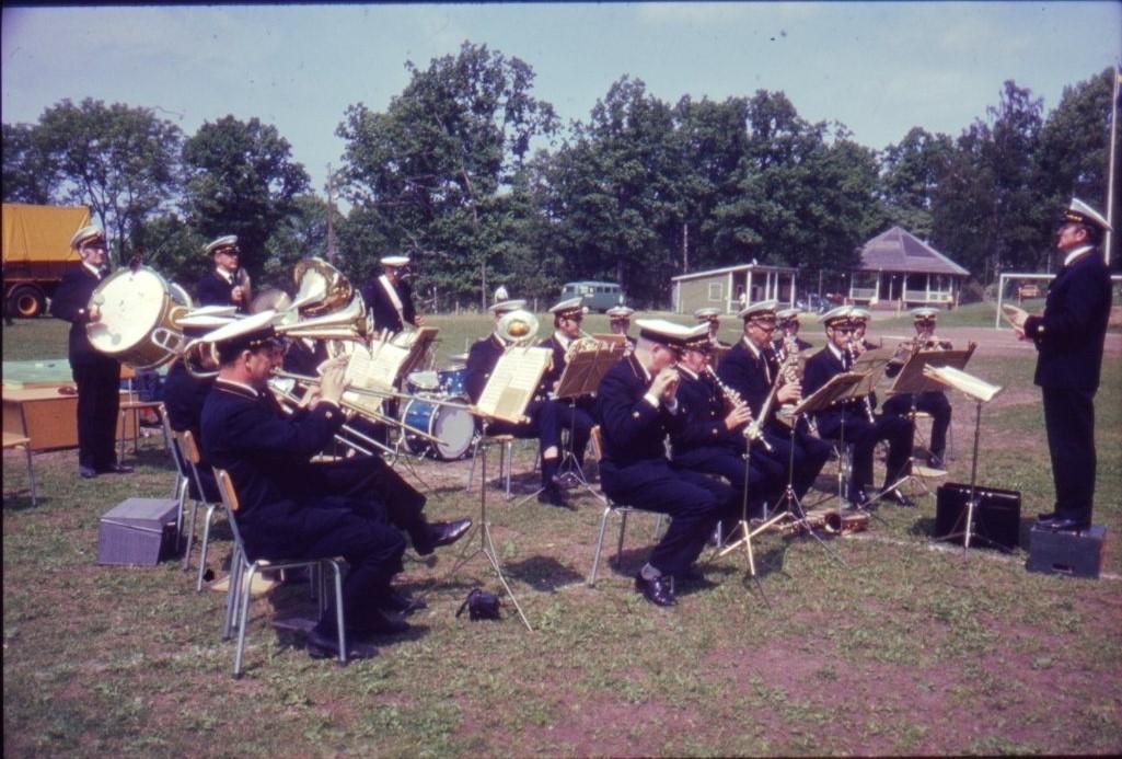 En blåsorkester i enhetlig uniform sitter på stolar på Åsavallens gräsmatta och spelar. Diabild.