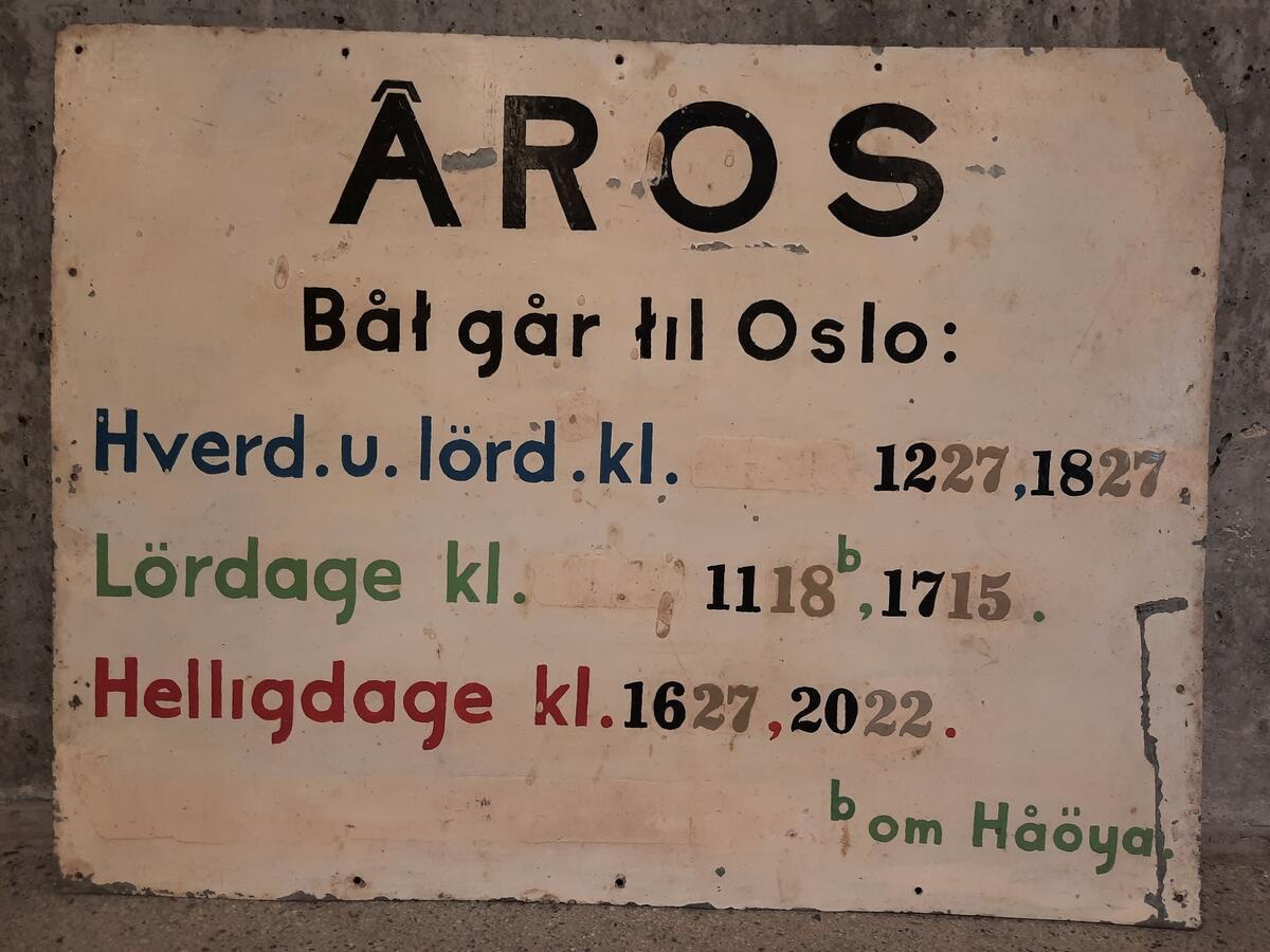 Skilt med båtrute til Åros. Skiltene er hvitmalte aluminiumsplater med svarte, blå, røde og grønne bokstaver. Skiltene er ikke mer enn 43 cm brede og 33 cm høye. Foto: MiA (Foto/Photo)