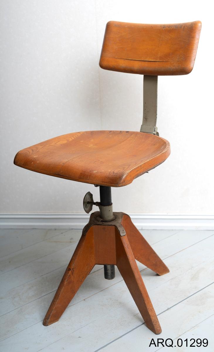 Kontorstol, lakket, med sete og rygg i tre, metallstang holder treryggen oppe. Beina er laget i tre med metallfeste.