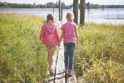 To jenter i rosa gensere går hånd i hånd på flåtegangen på Nordre Øyeren.. Foto/Photo