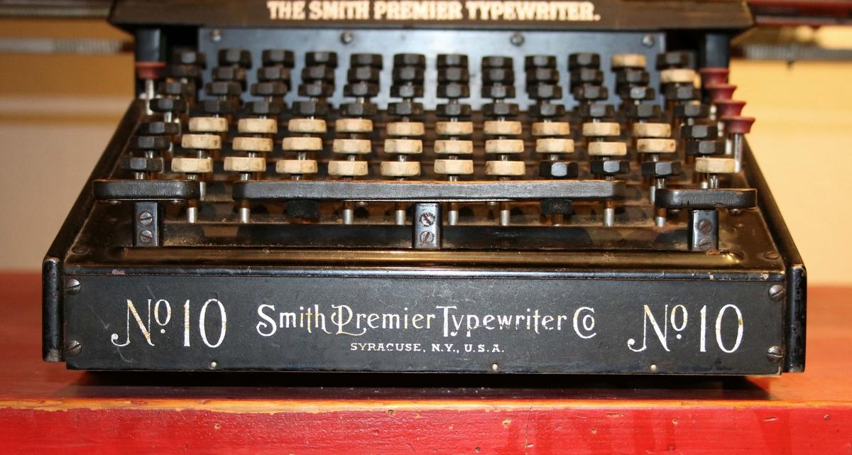 """Skrivmaskin. Svart, metall. Lång vals 690 mm. Stora och små bokstäver, öppen på alla sidor. Färgbandsskifte. Skalan graderad till 200. Märkt """"No 10 Smith Premier Typewriter Nr 10"""". Radskiftare på höger sida. Siffror på såväl höger som vänster sida.  Historik: Ada Damm – en av Borås stora historieberättare  Skribenten Ada Damm föddes i Stockholm 1869 men flyttade vid sju års ålder till Borås. Hennes far, August Charles, hade då fått arbete i staden som läkare. Hon var bland de första kvinnorna i Borås som fick utbilda sig vid elementarläroverket, därefter studerade hon språk, konst och musik i Stockholm.  I nästan 50 år skrev Ada Damm i Borås Tidning om livet och människorna i 1800-talets Borås. Materialet hämtade hon från arkiv, brevsamlingar samt genom att intervjua äldre boråsare. Människoöden, händelser, vardag och fest skildras i hennes berättelser. Ofta handlar berättelserna om stadens över- och medelklass. Med sina artiklar och böcker är Ada Damm en av Borås främsta historieskildrare.  Vid sin bortgång 1961 skänktes Ada Damms skrivmaskin och en fåtölj till Borås Museum.   """"Jag vet inte vad jag skulle ta mig till, om jag inte fick skriva. När jag känner behov av avkoppling sätter jag mig vid skrivmaskinen."""""""