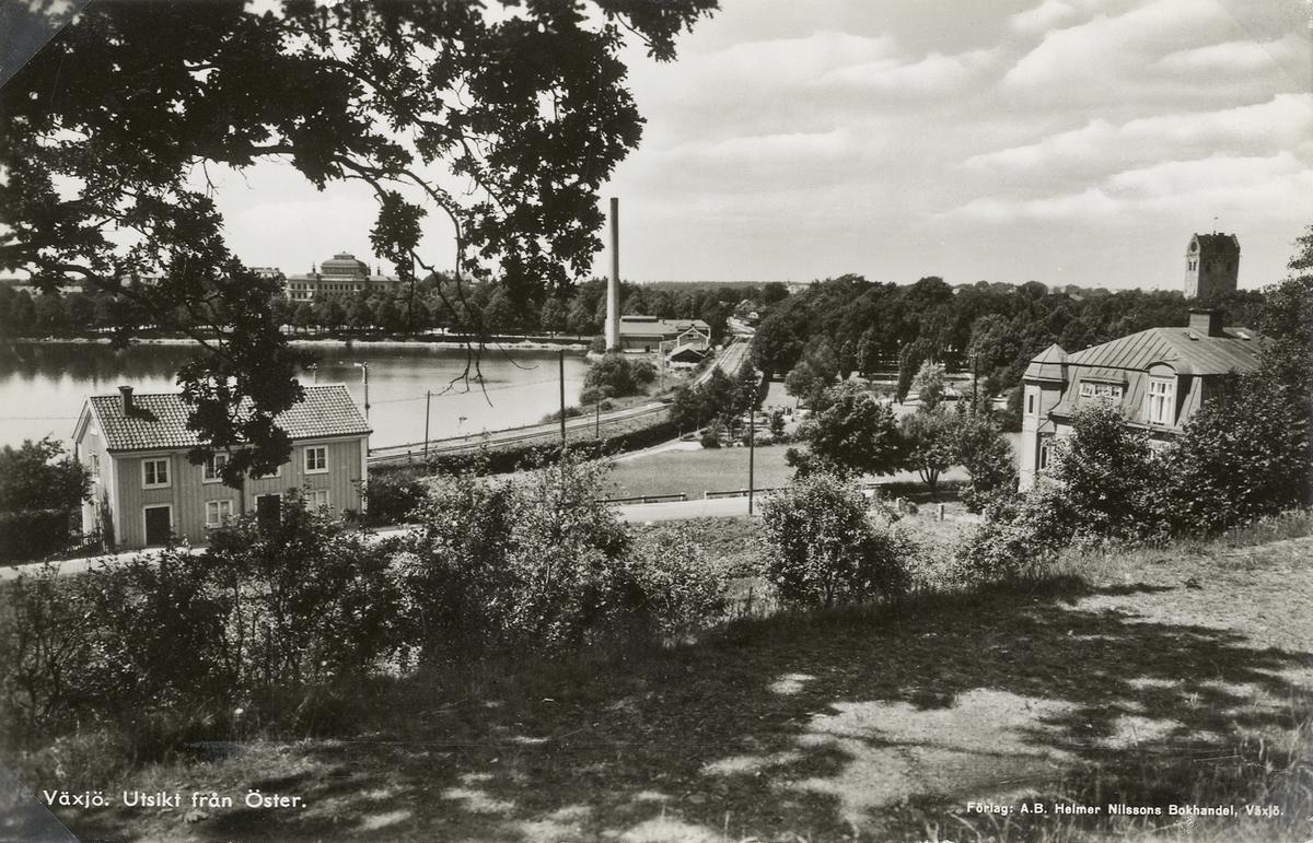 Växjö. Utsikt från Öster, 1939. Man ser Växjö läroverk, järnvägen och dåv elverket utmed Växjösjön.Till höger syns också tornet på domkyrkan. Vykort.