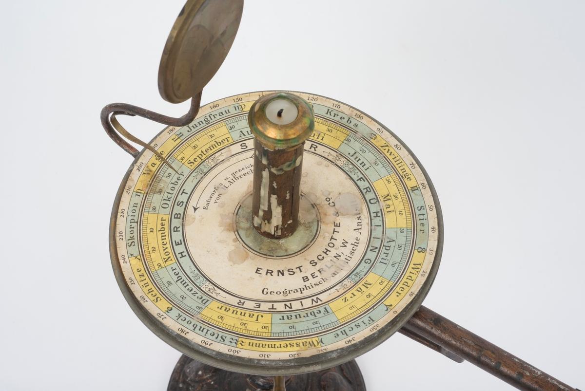 Modell med jordkloda og månen. Et stearinlys i en lysestake representerer sola. Ved å sveive håndtaket setter en igang mekanikk som demonstrerer jordas gang rundt sin egen akse og sola, og månens gang rundt jorda. En rund kalender med årets måneder, årstider og astrologiske stjernetegn ligger rundt lysestaken.