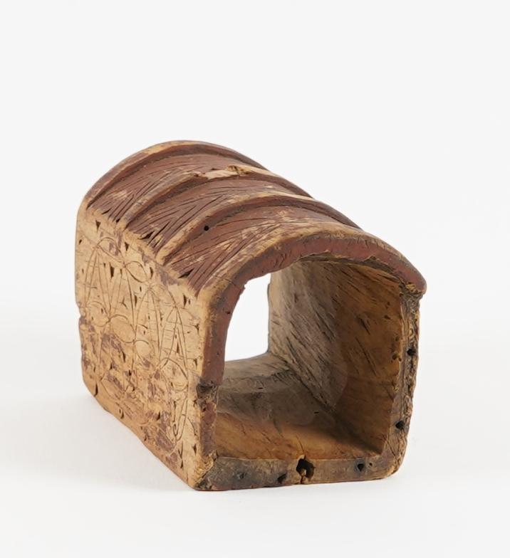 Ei bokforma øskje. Sjølve øskja er skore ut i eitt stykkje tre. Øskja har hatt to lok, eit i kvar ende, men har ingen no. Øskja er dekorert med karveskurd.