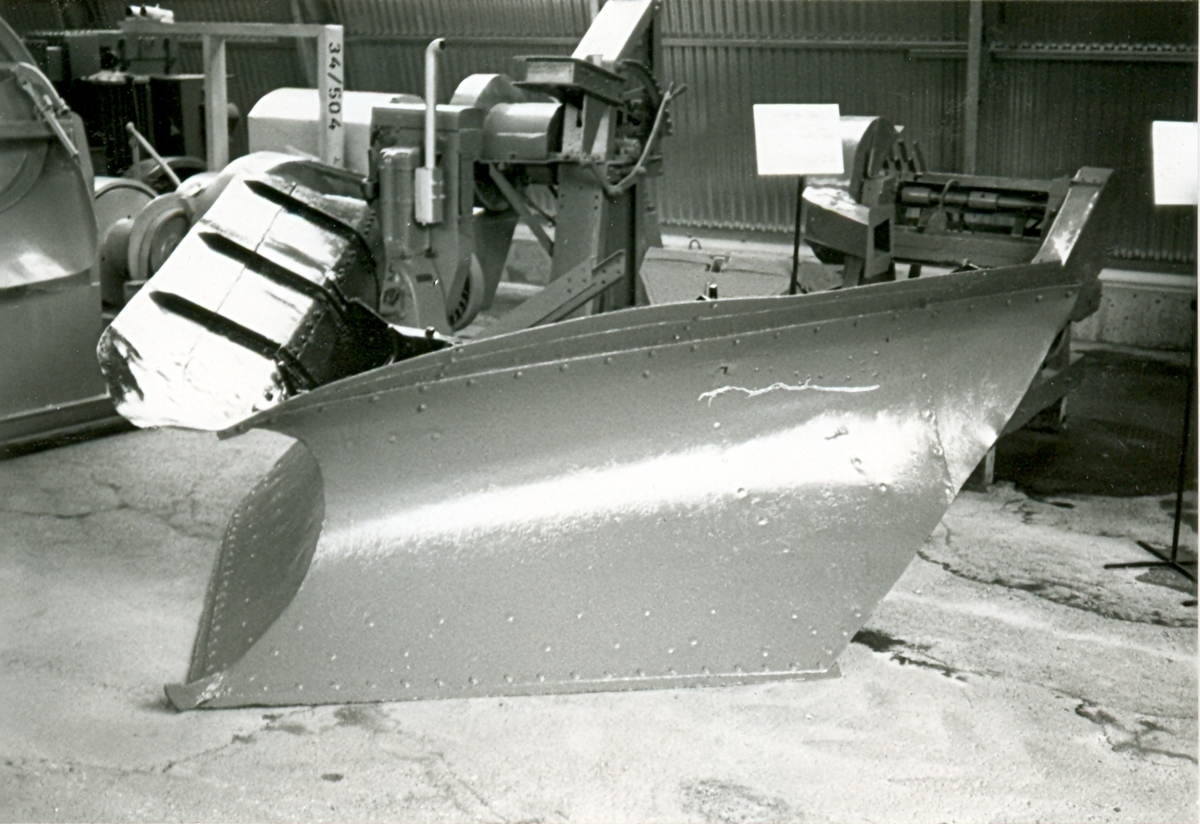 Spetsplog med plogsidan rödmålad, insidan och fästanordningar svartmålade. Fästanordnigar mot lastbilsfronten saknas i stor utsträckning. Fasta plogskär. Senare märkt på insidan, med fastnitade tecken, D2 nr 15.   Tillverkare: Arbrå verkstads AB Typ: 36 storlek 2 Nr: 2141 År: 1937 Märkt: D2 nr 15