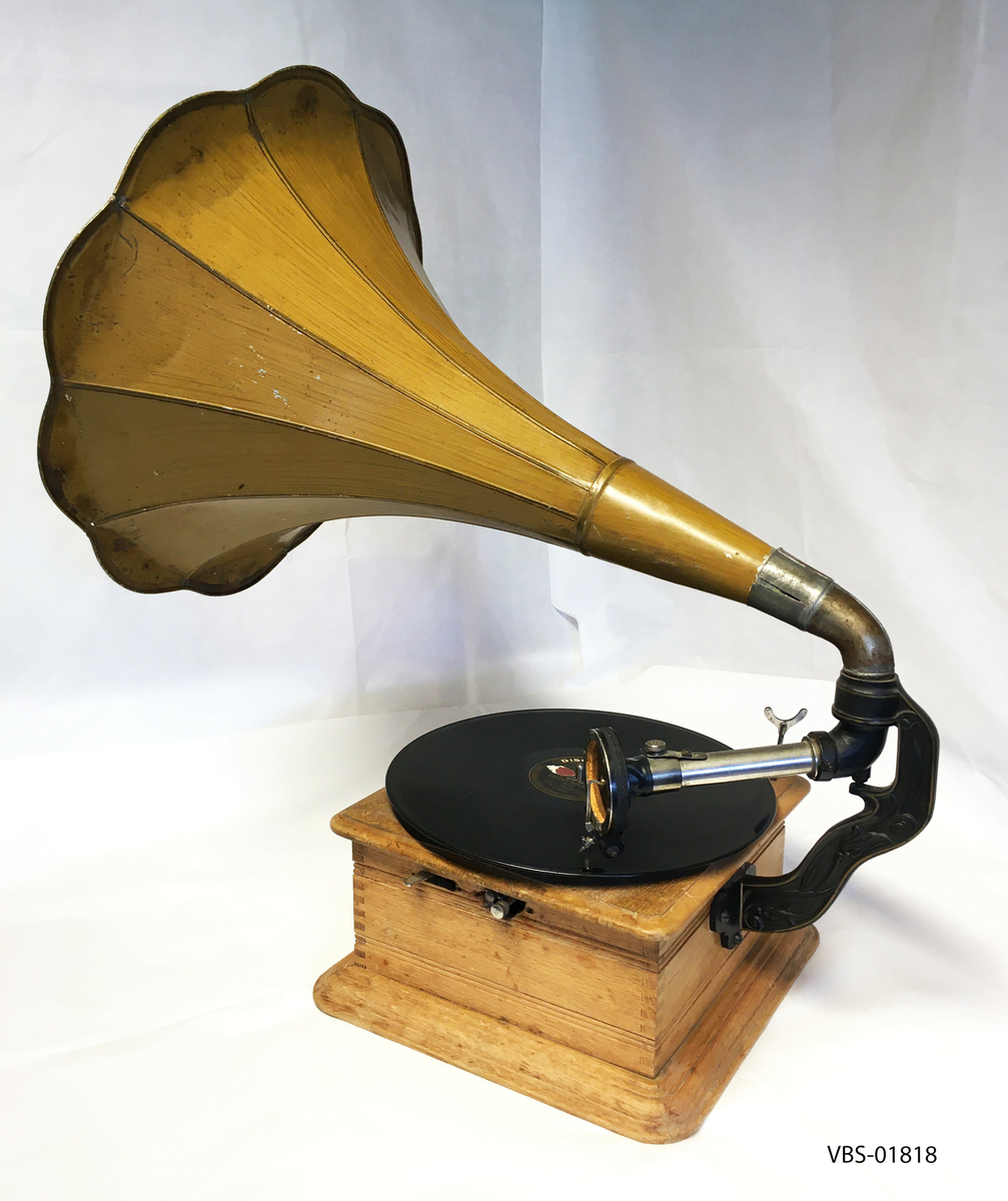 """Excelsior sveivegrammofon med bakmontert blomsterhorn (høyttaler). Gjenstanden er ufullstendig: Instrumentets nedre deksel mangler, og den interne mekanismen med motoren, veivene og andre deler, holdes fra hverandre (VBS-01818-1) Boksen er laget av eik og er ubehandlet. På forsiden er det Excelsior-emblemet. Den grønne filten er bevart på platespilleren, sammen med en grammofonplate: DISQUE PATHE. """"Si mes vers avaient des ailes""""- par le trio ACKROYD."""