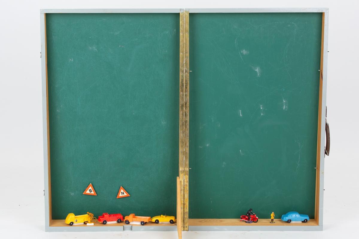 Materiell til trafikkundervisning. Tavlekasse som inneholder biler, skilt, trafikkillustrasjoner. Kassen fungerer som tavle og som stativ for plansjer.