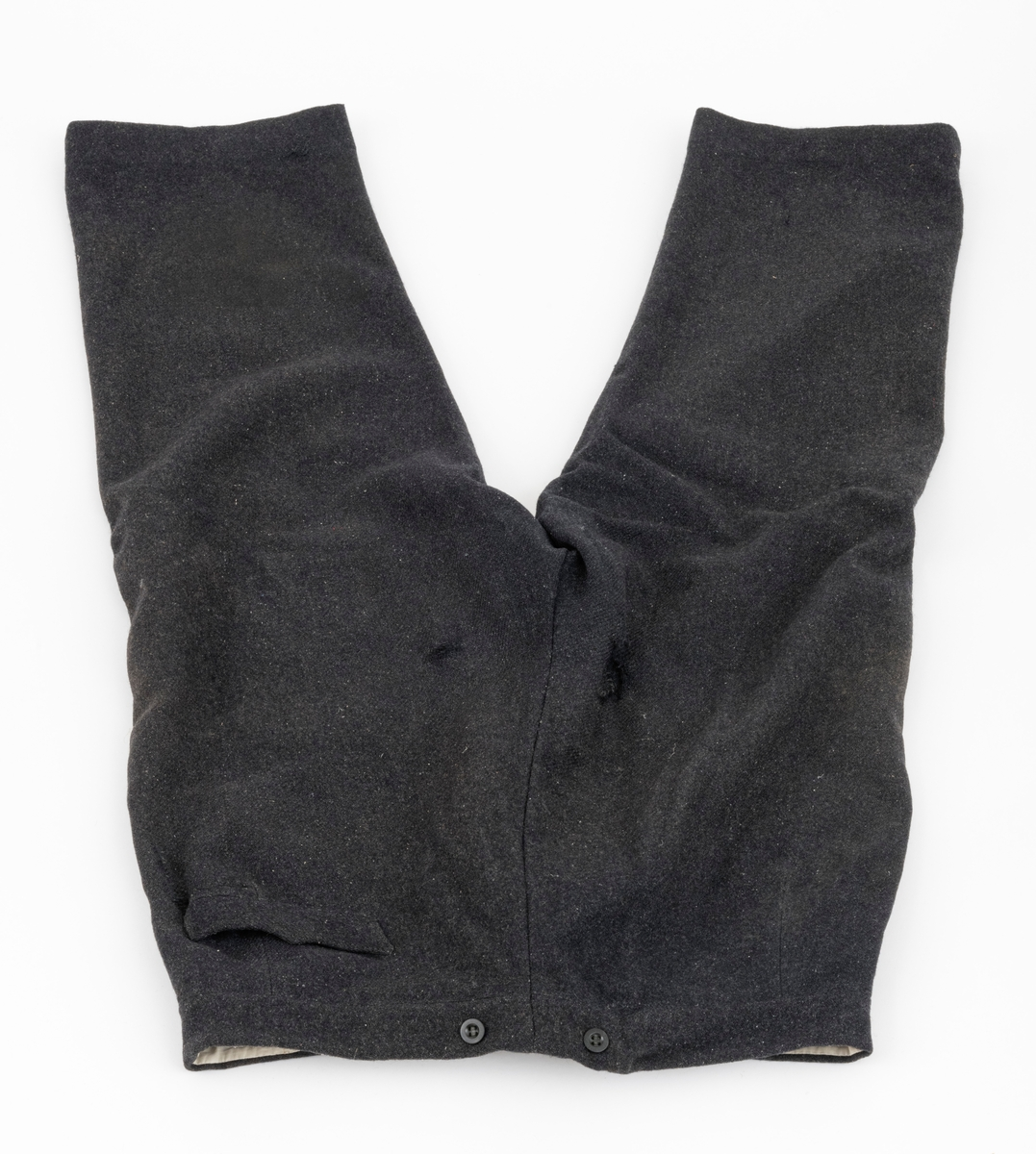 Bukse i svart vadmel (vevd ullstoff), med to stikklommer foran og en baklomme. Foret i den ene lommen foran er ødelagt. Det er påsydd 7 knapper i linningen. Den ene knappen brukes til åpning og lukking av buksa. De andre knappene, 4 foran og 2 bak, brukes som feste for bukseseler. Gylfen er utstyrt med 4 knapper, tre av plast en av metall.  Foran er det en åpning på 29 cm, som åpnes og lukkes med 4 knapper i gylfen og en knapp i linningen. Knappene er festet slik at når buksa åpnes og lukkes blir det omslag. Vadmelsbuksa er preget av bruk og slitasje. Begge buksebeina er bøtt foran, og det er slitt hull flere steder foran og bak på buksa.