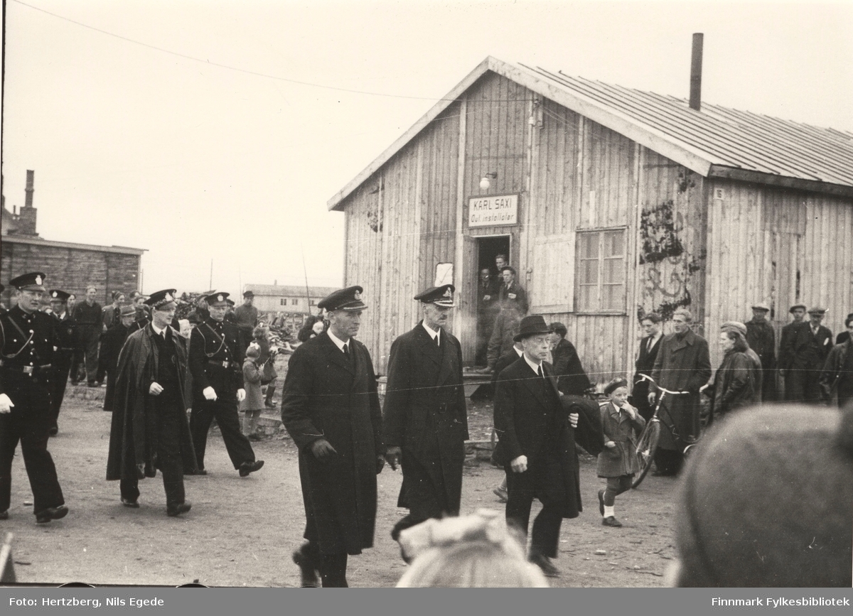 """Kong Haakon VII på besøk i Vadsø i 1946. Kong Haakon i midten, høyre siden går fylkesmann Hans Julius Gabrielsen. Mange mennesker står langs veien å ser på. Her går de forbi butikken til Karl Saxi """"autorisert installatør"""". Se også bildene 264-267."""