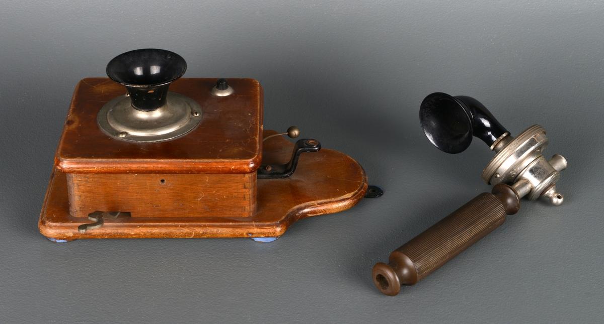 Veggtelefon, 2 deler. Laget i tre, metall og plast. Trekasse med høyttaler på og håndtak med mikrofon og tut. Ledningen er borte så delene henger ikke sammen, håndtaket på telefonrøret mangler en del.