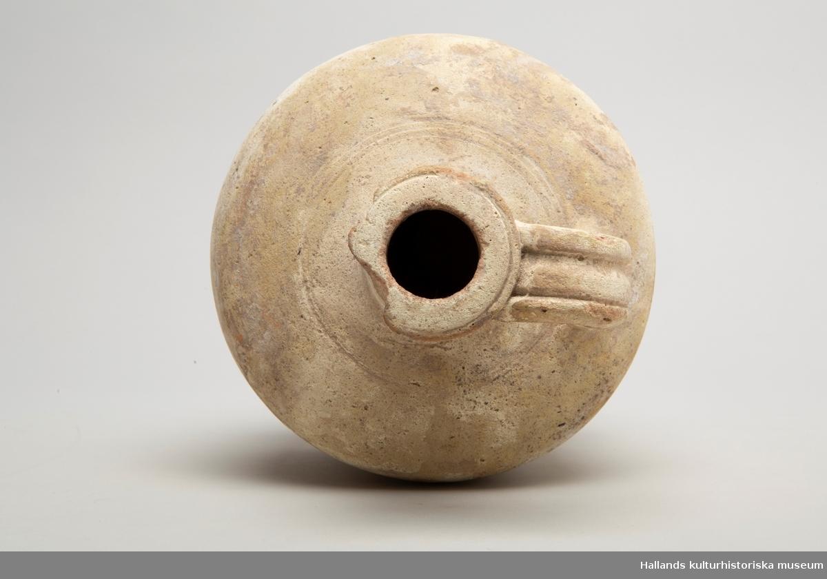 Karaff av keramik. Rund med smal hals upptill. Handtag fäst vid hals och behållare. Brätten vid öppningen. Randdekor. Delar av brättena borta.