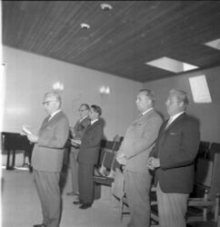 Profiler av fem herrar som står på en scen och sjunger.