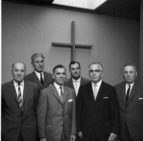 Sex herrar i mörka kostymer och slips står uppställda framför ett kors. Som nr 2 står Rickardsson, som 4 Olofsson och som 5 Svensson.