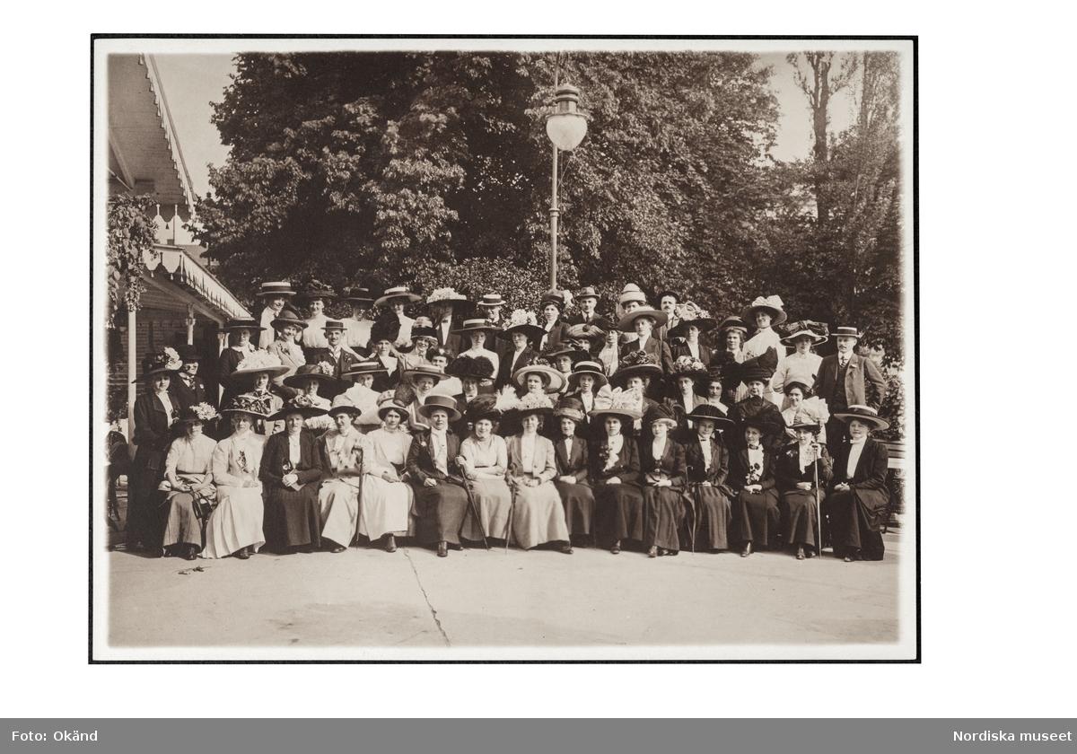 Ett grupporträtt av personalen på NK:s Franska damskrädderi på utflykt 1911. En grupp med sittande kvinnor i dräkt och hatt flankerade av några kostymklädda män. Den unge mannen längst bak, sjätte från vänster är Kurt Jacobsson, då nittonårig volontär hos Madame Suzanne.