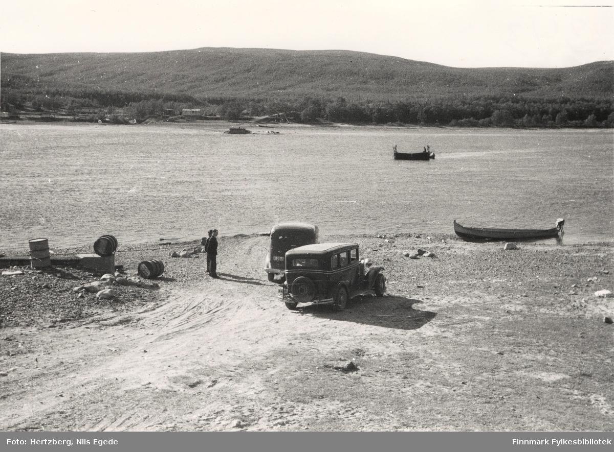 Seida fergested. Seida ferge er på tur over Tanaelva, 1948. Til venstre ser man et fundament for bukkebrua som ble satt opp i 1939. Ved elva ligger en elvebåt. På land står to biler. To menn står ved siden av bilene.