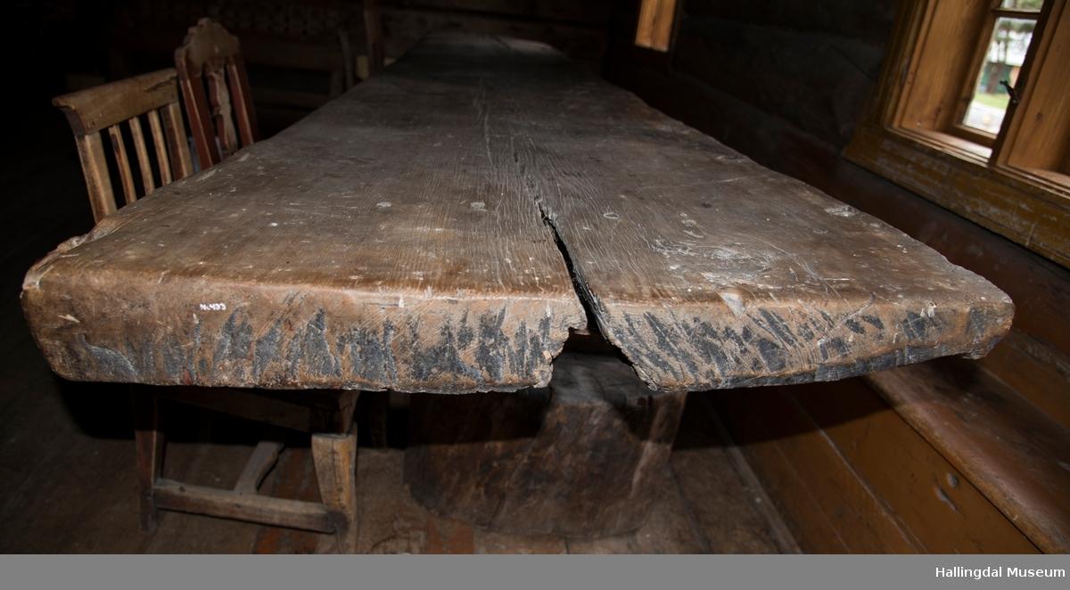 Langbord som består av en planke.  Platen er sprukket i begge ender, mest i den bredeste, der det på undersiden er satt på en 32 cm lang bordbit for å holde platen sammen.  Bordbiten er festet med fire sirkelrudne trenagler, bordbiten på undersiden mangler. Oppl. i gml. prot: Planke som etter sigende skal ha tilhørt Nes gamle Stavkirke v/ Fru Sidsel Tandberg. Bordplaten står på 2 store tilhogde stabber HFN 00434 a-b.  Bordet står i Toenstugu.
