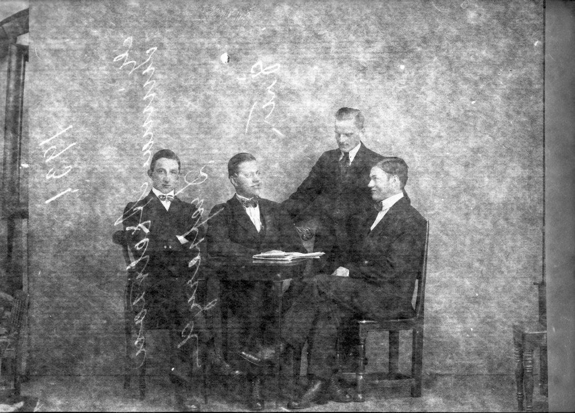 Fyra unga män sitter respektive står runt ett litet bord där det ligger en tidning. Som tvåa sitter Herbert Jansson från Udderyd och den stående mannen är Gunnar Axelsson från Drevseryd.