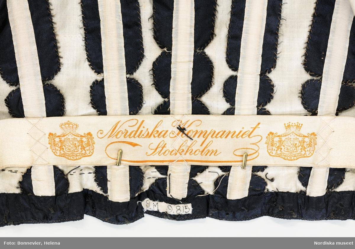Tvådelad svart sorgklänning i jugendstil monterad på docka. NK:s franska damskrädderi. Korsetterad dräkt i tidens S-silhuett med fotsid kjol. Beställd av Hanna Palme född von Born (1861-1959) samhällsaktivist, dräktreformist och farmor till Olof Palme, Sveriges stadsminister 1969-1976. Levererad ca 1902-1910. I Sörmlands museum, SLM 9815.