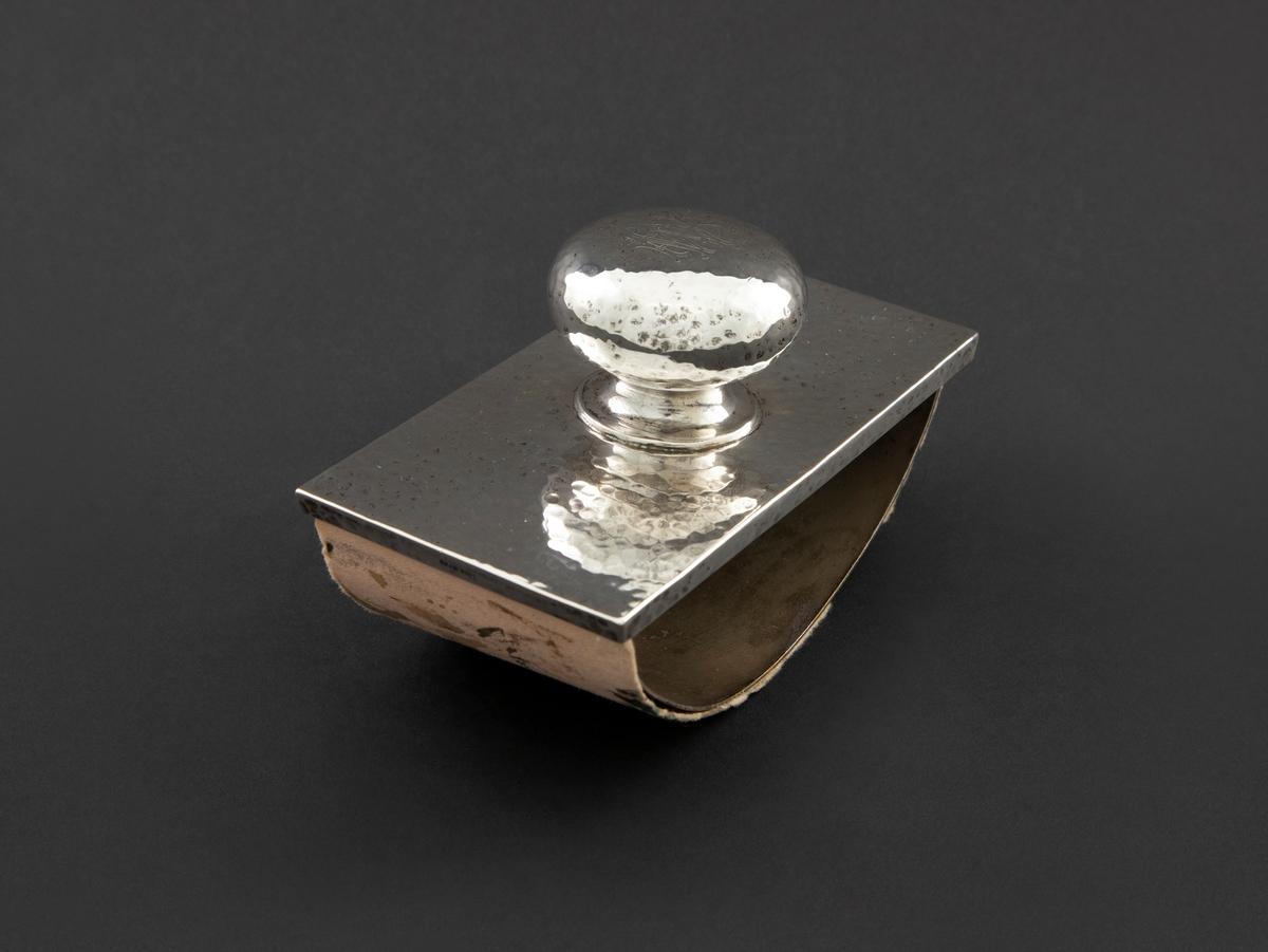 Løsjer i hamret sølv. Håndgrepet har flattrykt kuleform og er plassert midt på en rektangulær plate. Under har den en avrundet såle hvorpå et stykke trekkpapir er festet. Trekkpapiret er med rester av gammelt blekk med skrift av eieren, Fredrik B. Wallem.