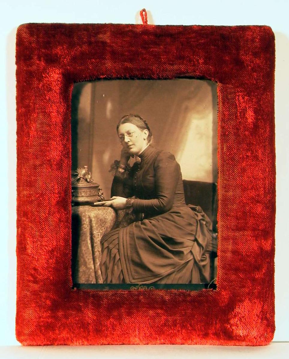 Fotografi av en voksen dame sittende med albuen på et lite bord støttende hode på høyre hånden og med en bok i venstre hånden hvilende på bordet. Hun har briller og oppsatt flette rundt bakhodet.
