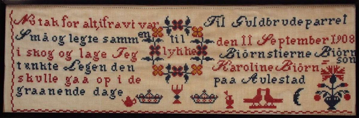 """Navneduk brodert i korssting på to-skaft bunn. Motivet er ulike figurer og """"Synnøves sang"""" med """"til lykke"""". Annenhver linje blå og rød. Nederst 2/3 av bredden brodert en rød kaffekanne, en r.b.krone, tre-armet lysestake, krone, rød kanne med åpent lokk, to røde fugler, speilvendte, blå månesigd og en r.b.urne med blomst, knopper og blad. Langs øverste kant en stikk-hullsfald, jar i begge sider. Nederst rød 3-stings siksakbord (flat) og sårkant av tøyet."""