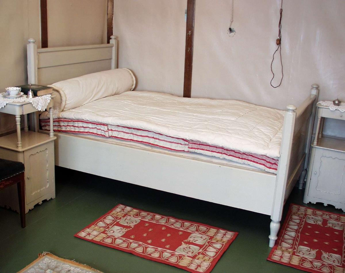 Hvitmalt seng med dreide ben og rette gavler.