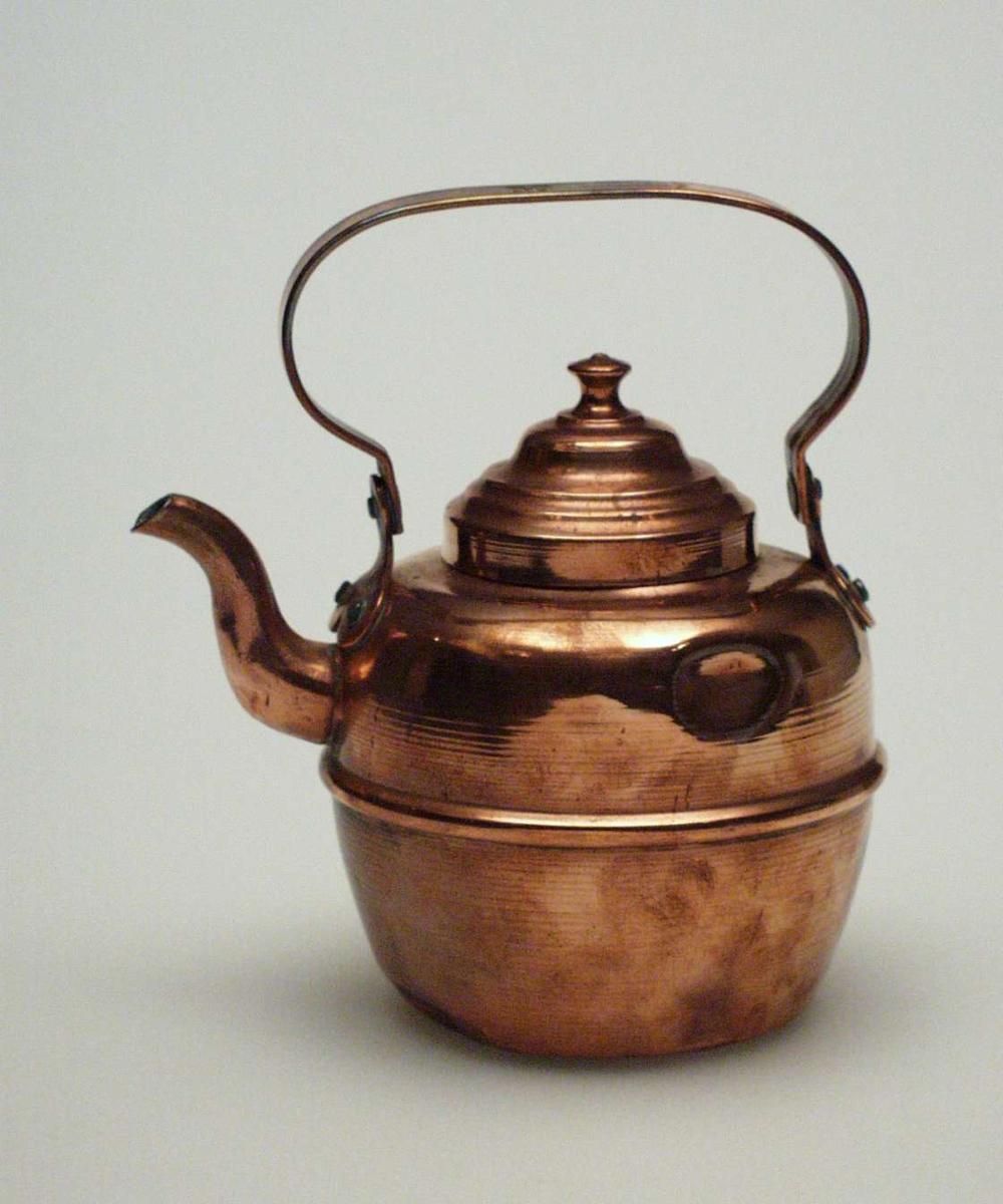 Kaffekjele i kobber med lokk. Den er beregnet til bruk på ovn. Pånittet hank. Lokket har riller. Kjelen er fabrikkprodusert. Den er presset ut av tynne plater, ikke hamret slik kobberslagerne gjorde det.