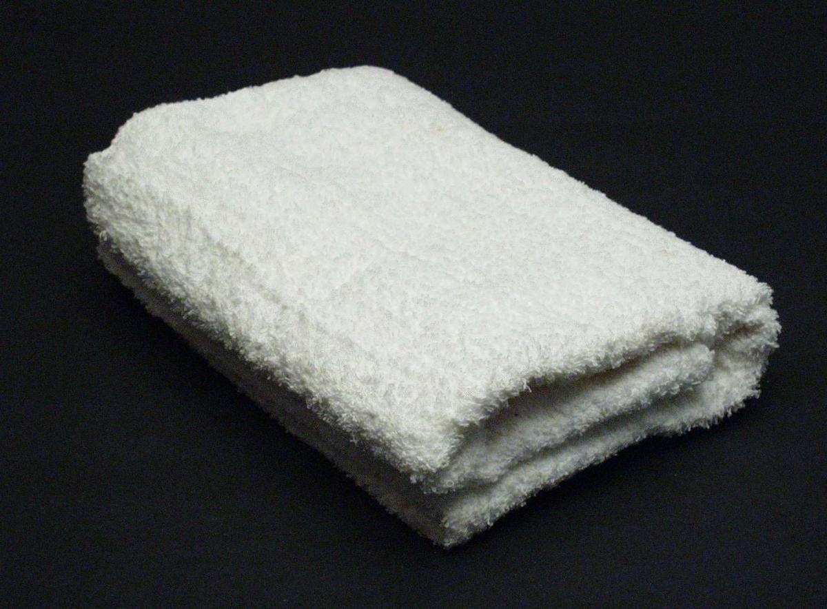 Hvitt håndkle i bomullsfrotté sydd til en ring. Maskinvevd metervare.
