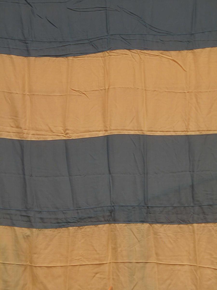 Flagg sydd sammen av horisontale striper i hvitt og blått. Påsydd løpegang med snor og metallring. Flagget er nesten kvadratisk.