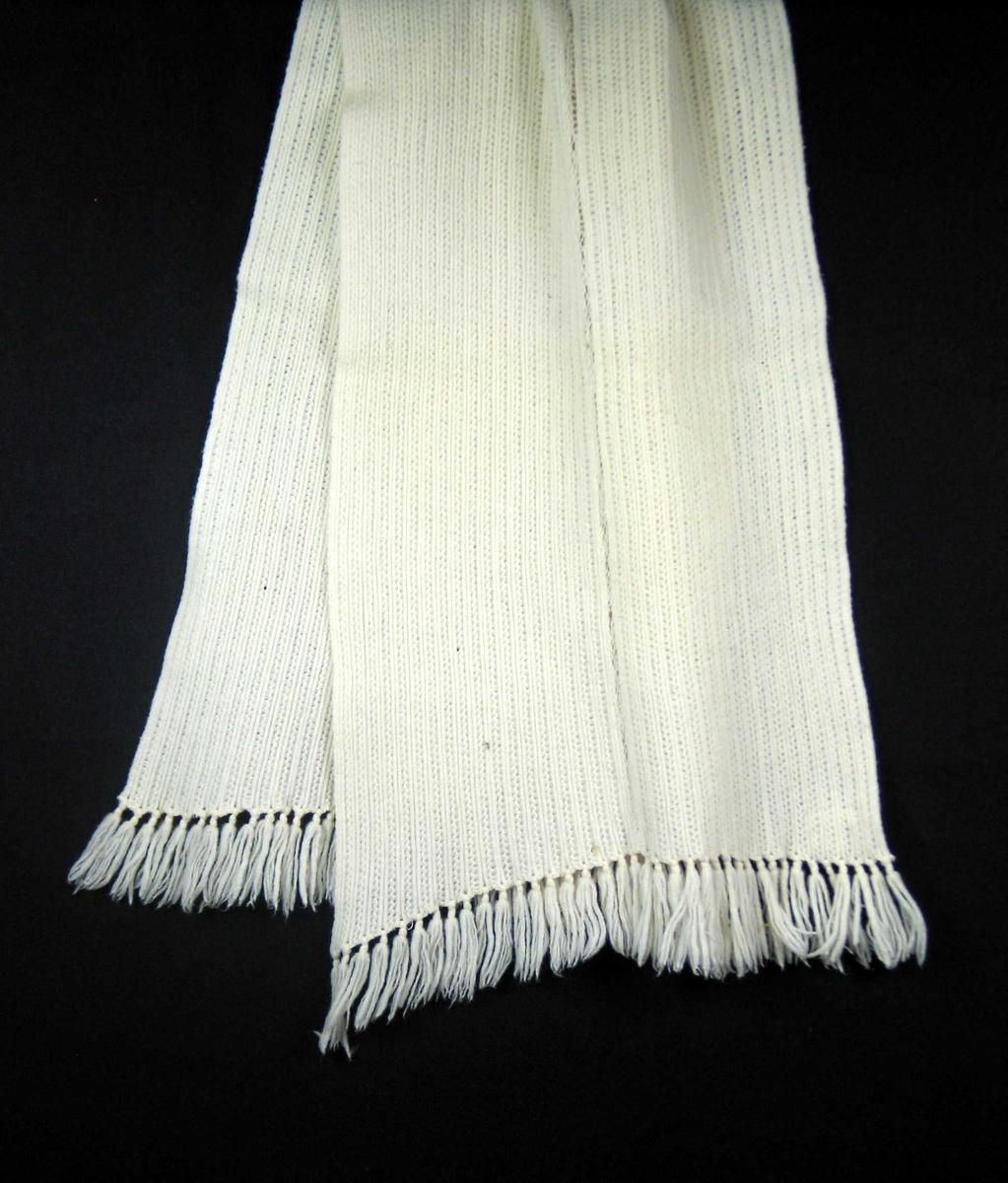 Hvitt maskinstrikket skjerf med langsgående ribber. Skjerfet er sydd sammen av to lengder. Tverrkanten er sydd med overkastingsmaskin og påsatt frynser med en knute.