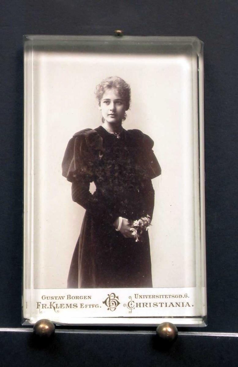 Portrett av ung kvinne i svart kjole. Hun holder hendene foran med blomsterbukett.