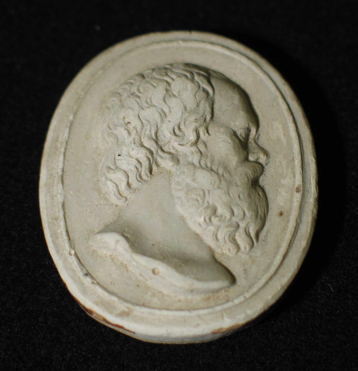 Oval medaljong i gips. Sokratesbyste i profil. Merker etter innfatning.