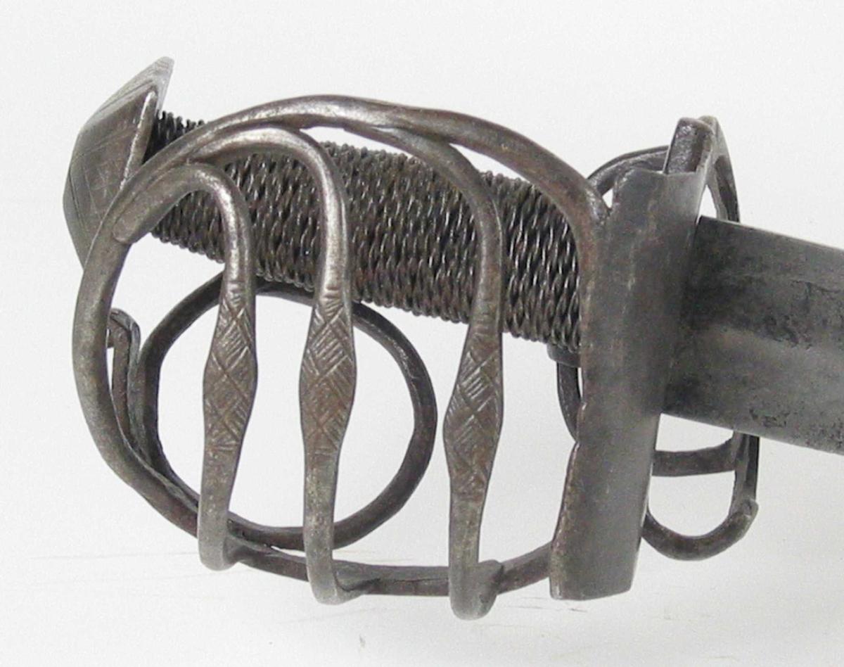Pyramideformet knapp med kryssfilt dekor. Asymmetrisk feste med tre sidebøyler på utsiden med kryssfilte fortykninger på midten. Innsiden har to sidebøyler, tommelbøyle og klingebrekker. Rektangulær parérplate på utsiden. Begge  parérstengene er brukket. Tregrep med jernvikling. Enegget krum klinge med smedstempel på venstre side. Klingen har bred hulslipning og gjeddenebb. Tidligere registrert som Stridsøks kfr. nr 5470 A