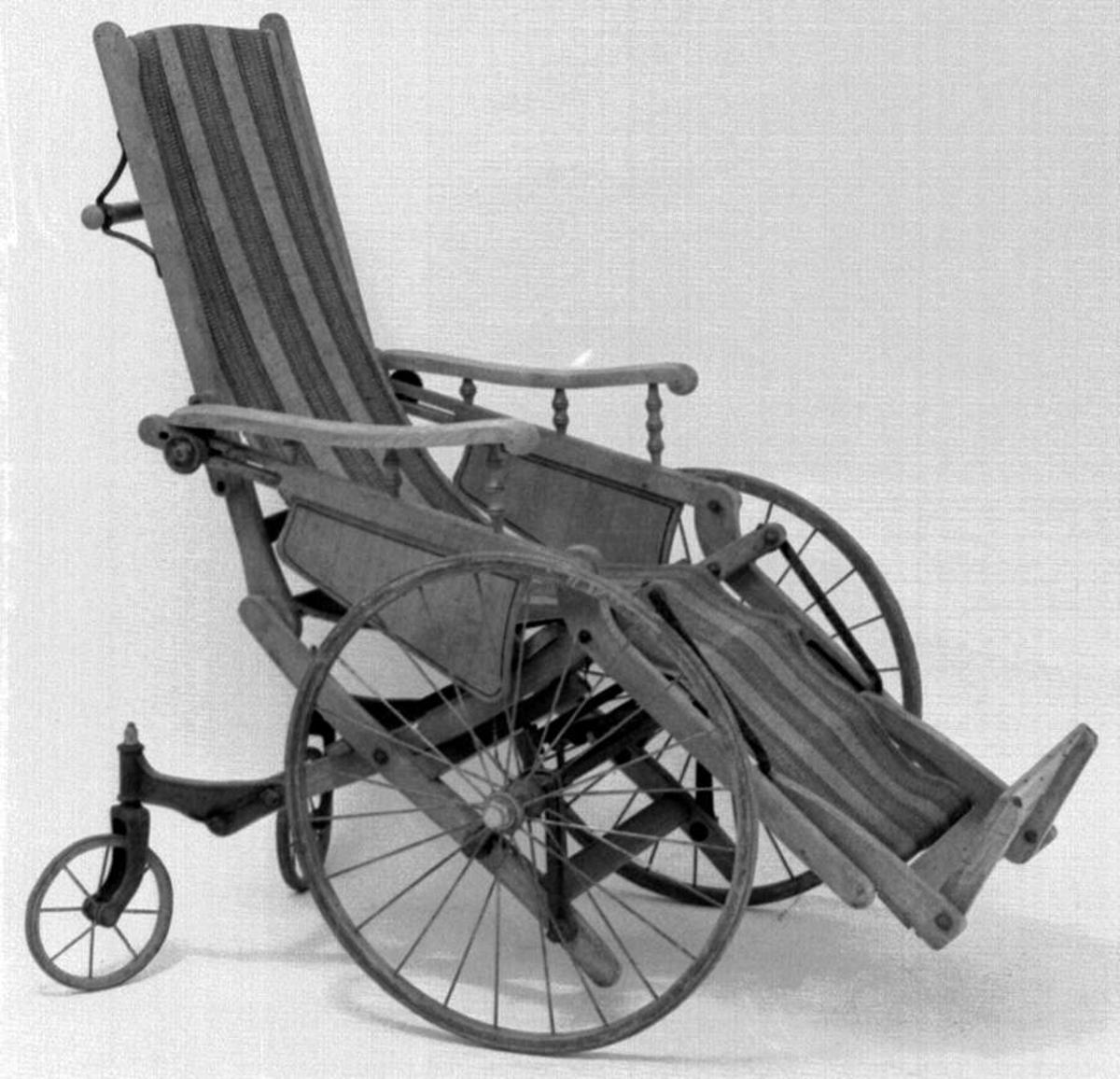 En rullestol av eik og bøk. Stolen har regulerbar ryggstøe og oppsvingbart fotbrett. Den har en strieduk i polykromet farge som er festet til fotbrettet og ryggstøe. Hjulene er forbundet med stolens treverk, og er to små og store.