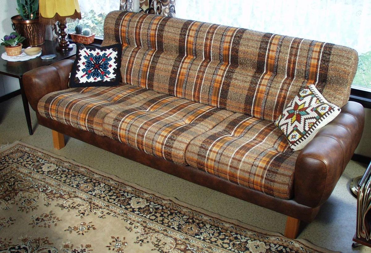 Sofa trukket i brun skai. Putene i rygg og sete er oransje- og brunstripete tekstil.
