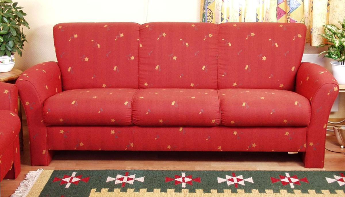 Sofa heltrukket i rødt stoff med gule blomster og grønne blad. Armlenene er buede og ryggen skråner lett utover. Sete og rygg har stikninger som deler sofaen i tre.