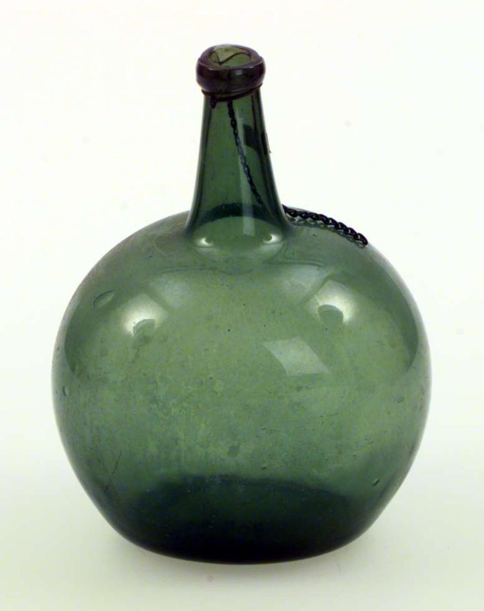 Karaffel i grønt glass. Den er flat på sidene. Rundt halsen henger det en metallenke.