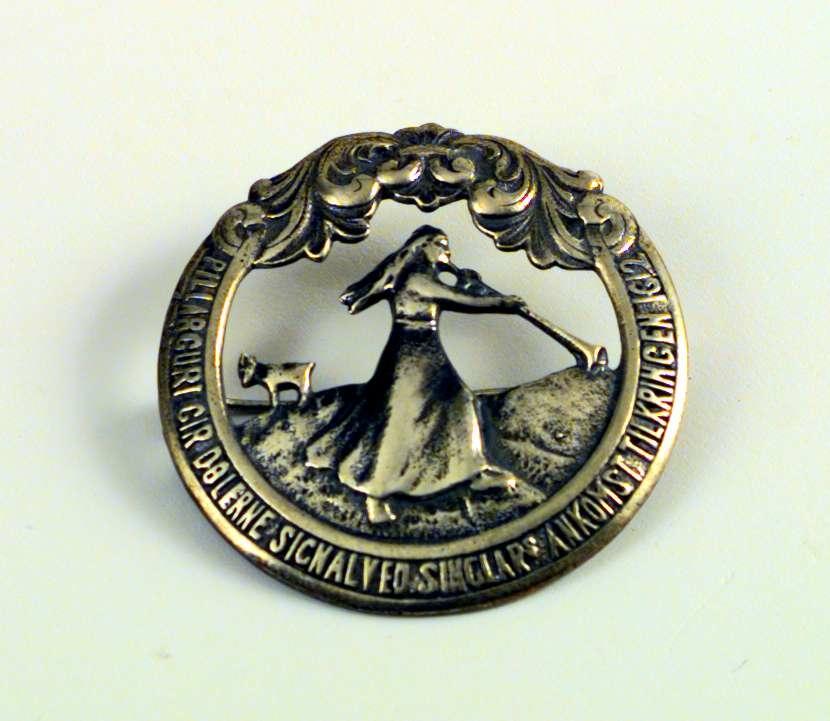 Brystnål eller brosje i sølv med Pillarguri-motiv. Nålen ligger i en eske fra gullsmed J. Frisenberg. Esken er lys blå.