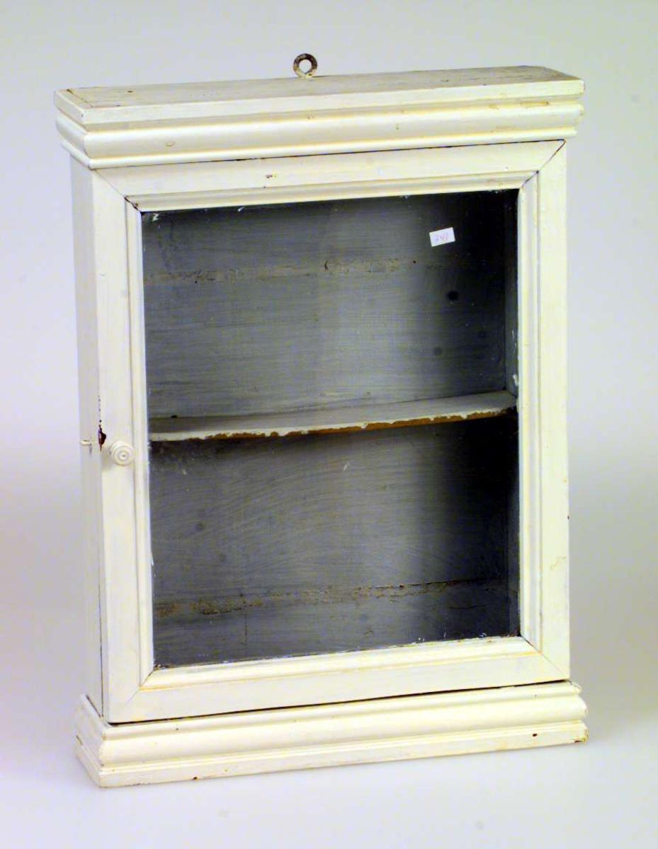 Lite, hvitmalt hengeskap med én hylle. Det er glass i døren. Døren er høyrehengslet. Det er en øyekrok som oppheng.