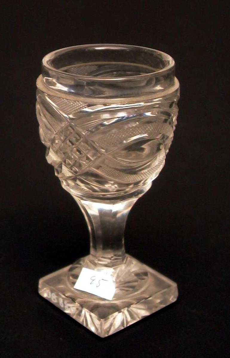Tykt vinglass med firkantet fot. Det er små hakk i foten.