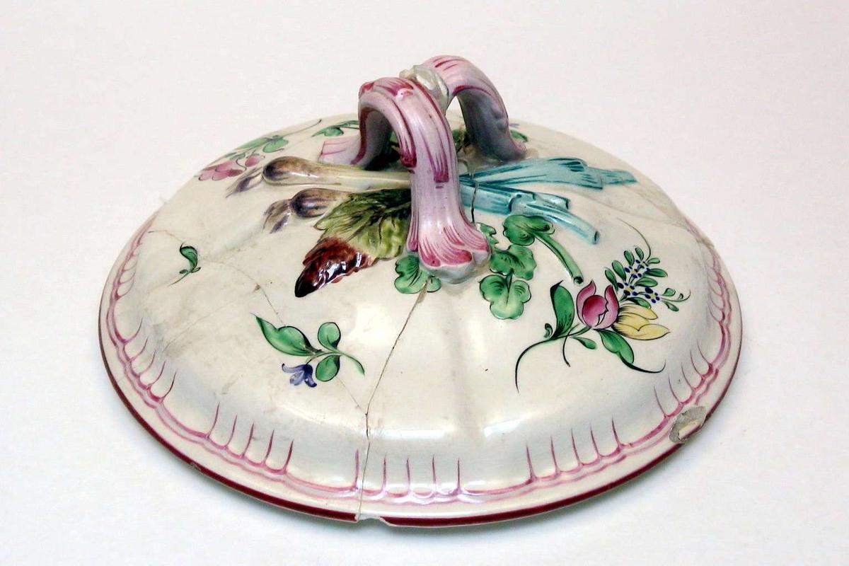 Rundt lokk i kremfarget keramikk med polykrom blomsterdekor. Lokket er defekt. Fatet eller terrinen som lokket har hørt til, mangler.