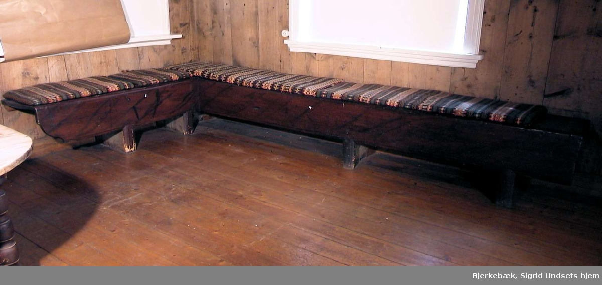 Veggfast benk i vinkel. Benken er malt brun med sort ådring. Malingen er slitt. På benken ligger det to lange og to kortere puter med vevd stoff.