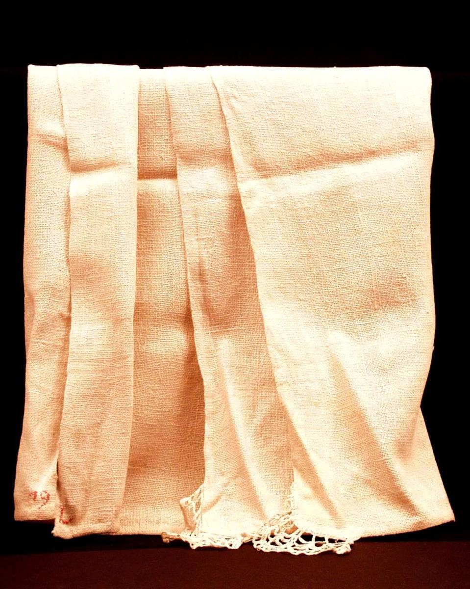 Benkeduk eller alterduk (?) i hvit grovvevet linstry. Jare i to sider. 1 cm håndfald i kortendene. I to hjørner er det påsydd, rynket, kjøpt blonde. Monogram L 19 i rød korssting.