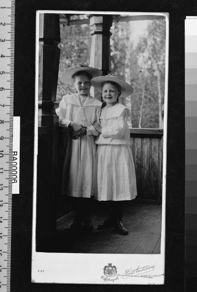 Barneportrett; to store piker med støvler og hatt - med stor skygge og dekorasjon rundt hattepullen. Pikene står på en overdekket veranda med naturen som bakgrunn.