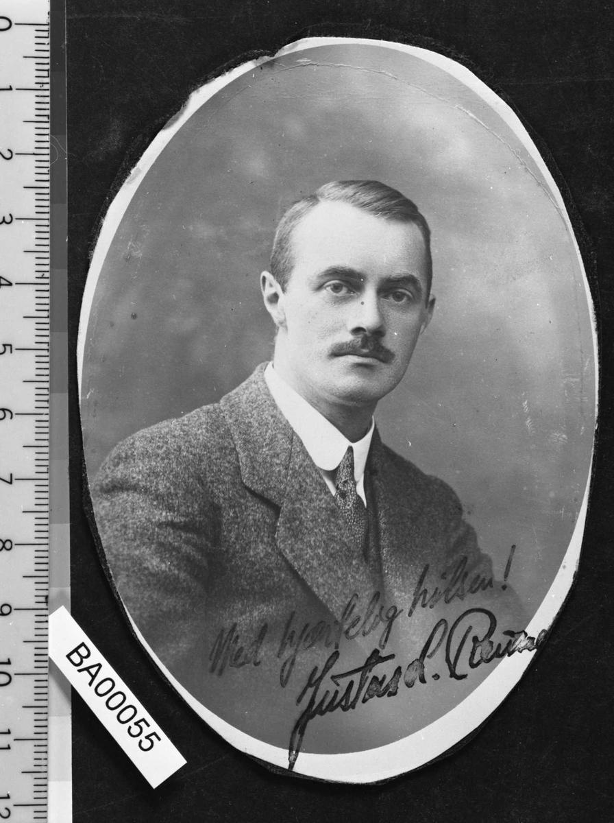 Portrettfotografi av en voksen ung mann med glatt vannkjemmet hår og liten pent klippet bart; kledd i nistret jakkesett med vest, hvitt skjorte med nistret slips. Han ser direkte på betrakteren. En hilsen med signatur er satt nederst på fotografiet.
