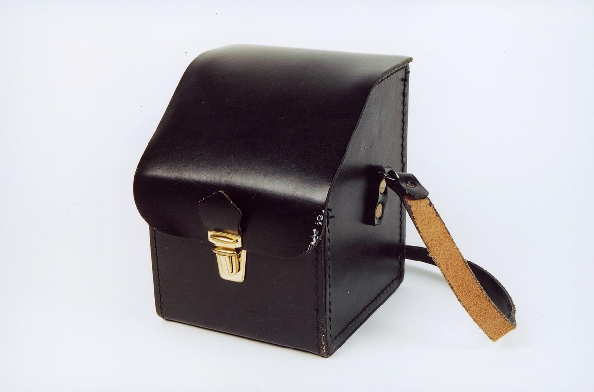Veske i lær med skulderreim for oppbevaring av innskuddstempel i Postbanken. Til bruk i landsposttjenesten ved innskudd i postbankbøker. Lukkeanordning i metall.
