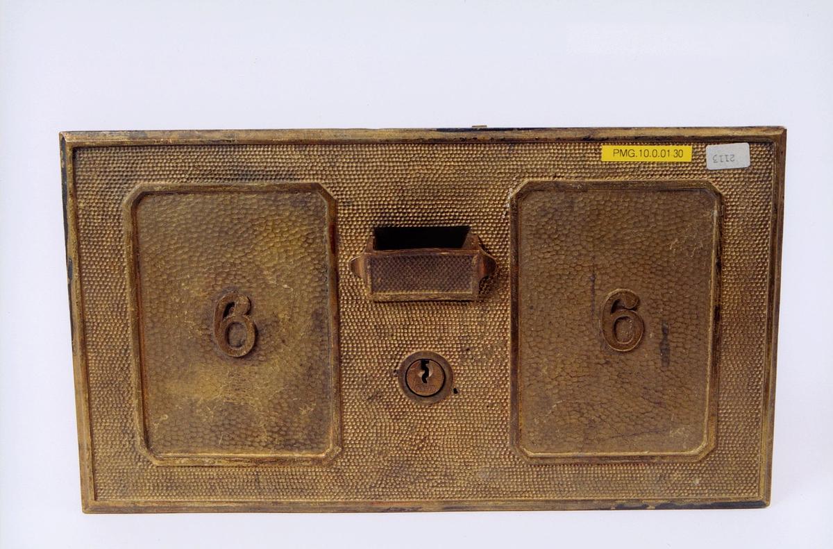 Postboksdør i metall med lås. Tallet 6 står på døren.
