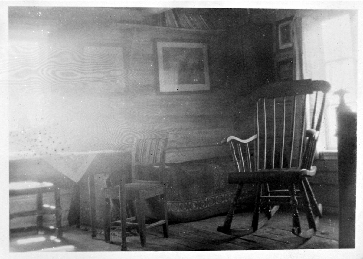 Interiør, tømmerhus, gyngestol, seng, bord,stoler