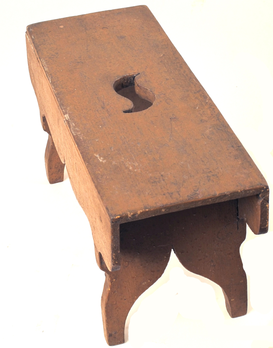 Krakk av furu,  malt oker  Krakk med S formet  handtaksåpning pm. Sidevanger med  hjerteformet spalte mellom benene.  Tilstand jan. 1967: endel fuktskadet,